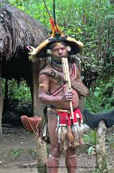 Huli wigman playing a flute Papua New Guinea