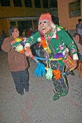 Masked dancer with a whip, festival at the village of Aguas Calientes, Andes Mts